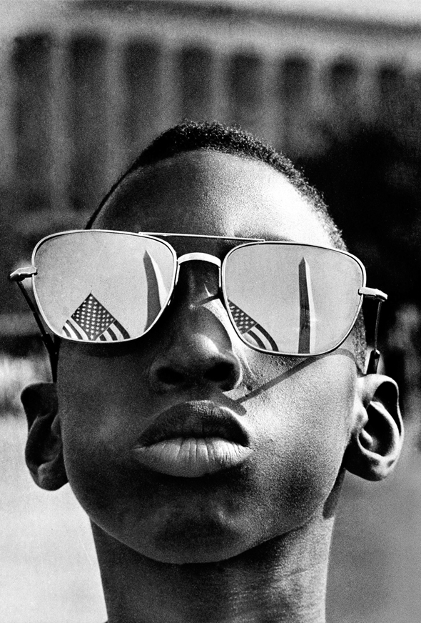 The Washington Monument and a U.S. flag are reflected in the sunglasses of Austin Clinton Brown, 9, of Gainesville, Ga., as he joins others in the March on Washington on Aug. 28, 1963 (AP Picture)